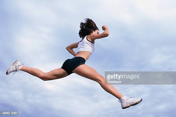 Woman in full stride, jumping