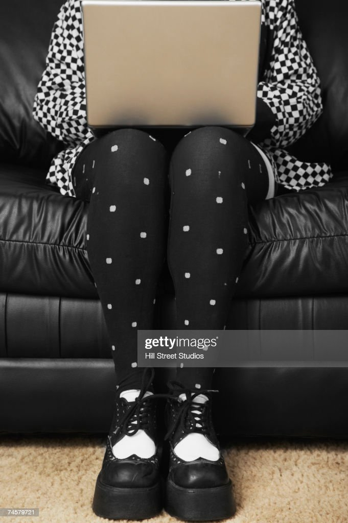 Woman in funky tights typing on laptop : Stock Photo