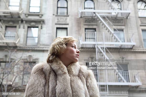 Woman in fur coat on street looking to side, low angle view