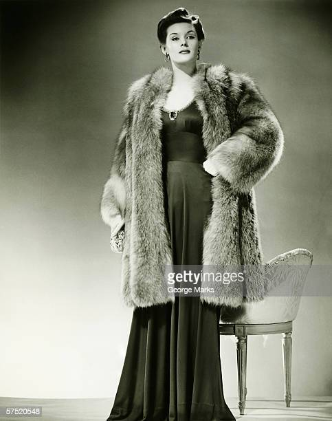 Woman in fur coat posing in studio, (B&W), portrait