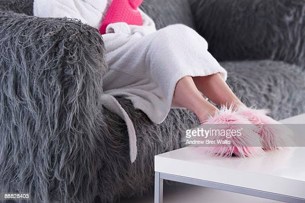 Woman in fuzzy slippers and bathrobe on sofa