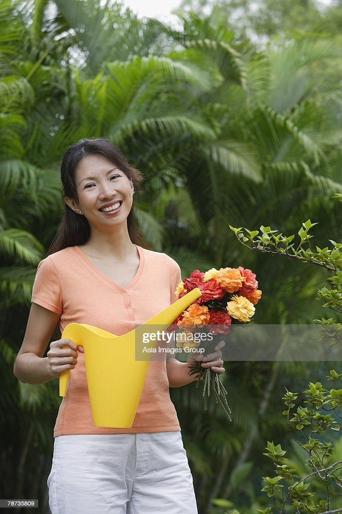 Woman in garden, holding bouquet of flowers and watering can