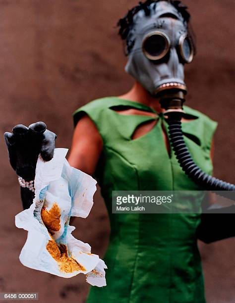 Woman in Gas Mask Holds Diaper