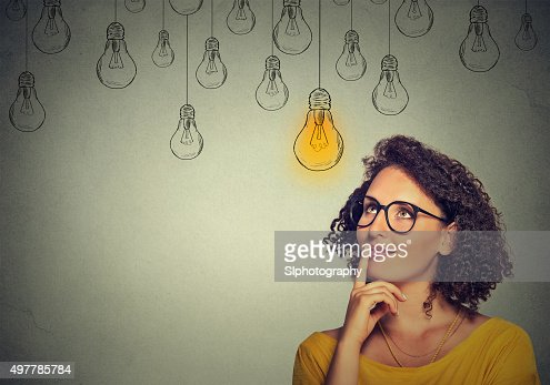 woman in glasses looking up with light idea bulb : Stock Photo