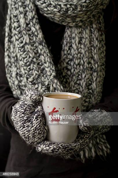 Woman in gloves holding a mug of coffeee
