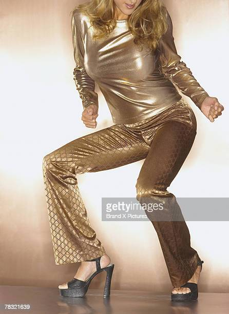 Woman in gold disco dancing