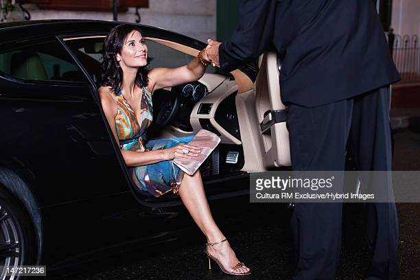 Woman in gown climbing out of car