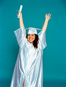 Woman in graduation robe with arms outstretched