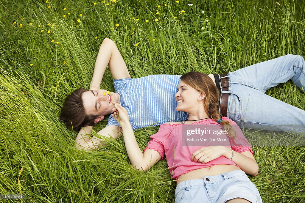 woman in grass, tickling boyfriend with flower. : Stock Photo