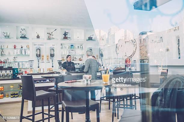 Frau in Grau und zwei weibliche Baristas, Caffe Triest, Europa