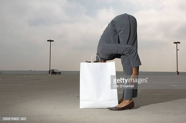 Woman in gray suit bending waist, head in shopping bag, side view