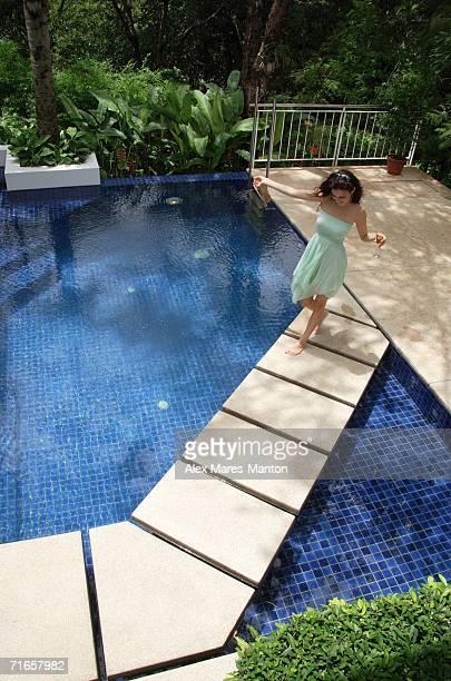 Woman in green dress walking across swimming pool