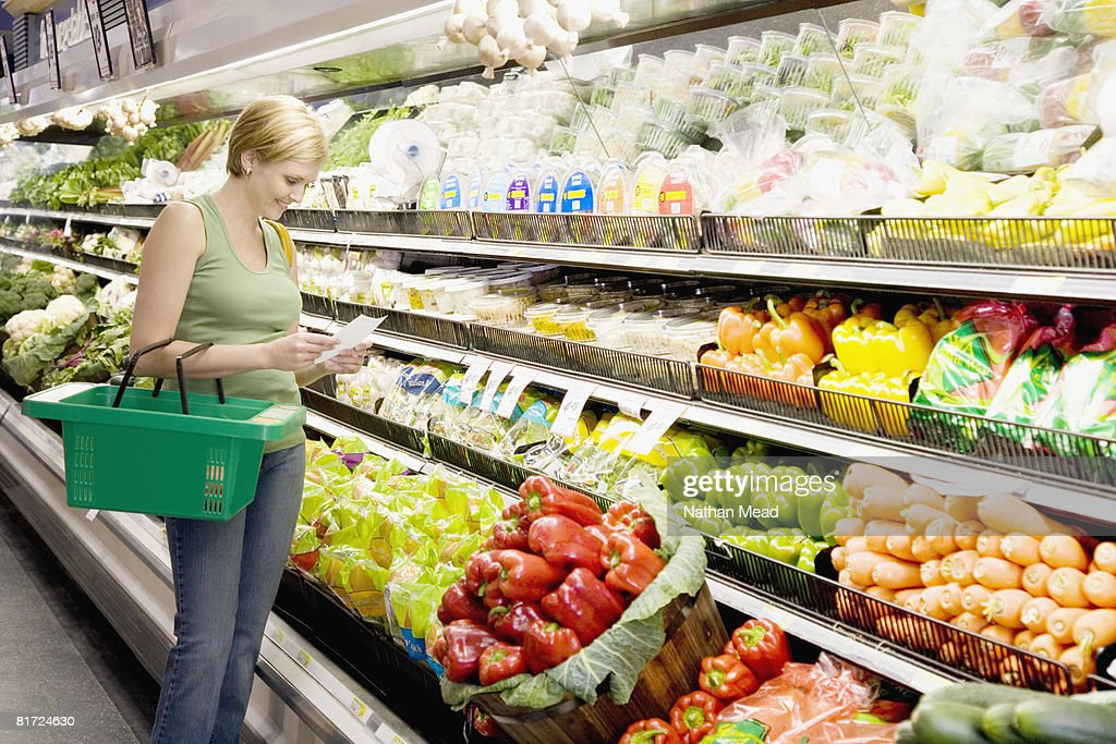 Woman in grocery store with shopping list smiling : Stock Photo