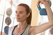 Woman in gym holding Kettlebell over her shoilder