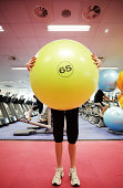 Woman in gym holding large exercise ball