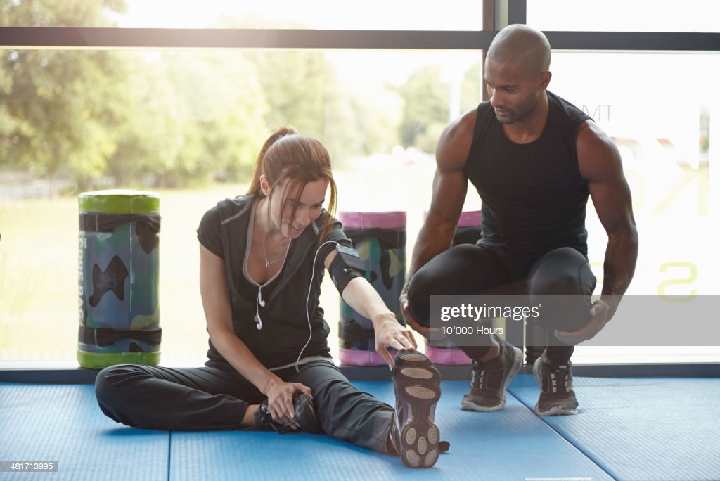 Woman in Gym stretching personal trainer watching : Stock Photo