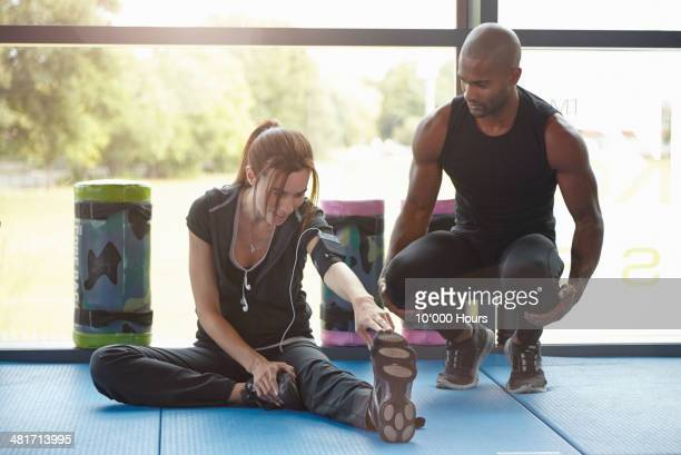 Woman in Gym stretching personal trainer watching