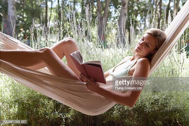 Woman in hammock reading book, side view