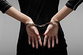 Woman in handcuffs (close-up, focus on hands)