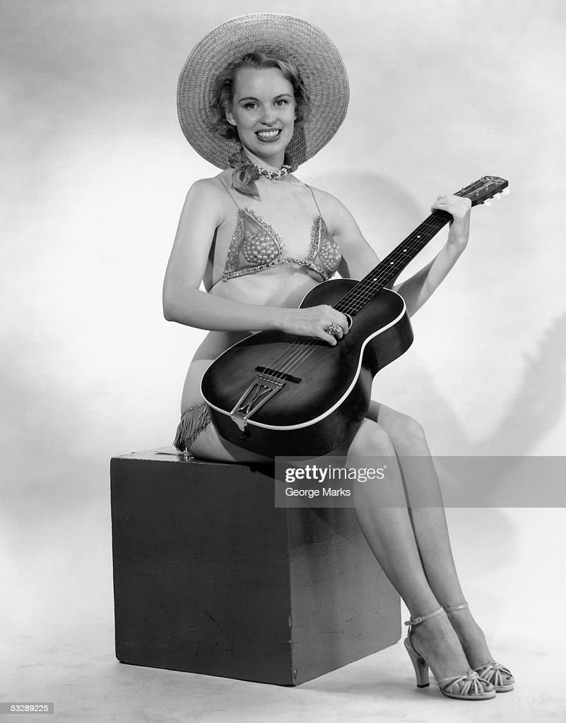 Woman in hat and bathing suit strumming : Stock Photo