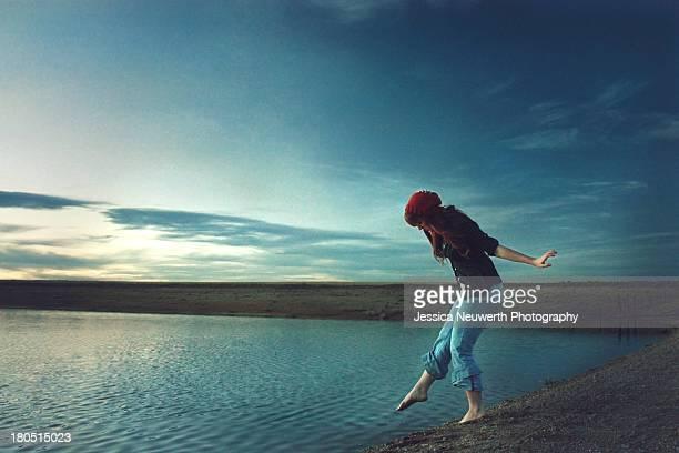 Woman in hat dipping toe in roadside lake