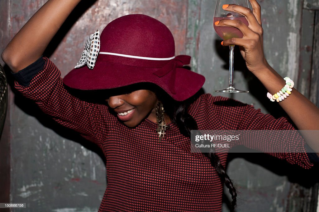 Woman in hat drinking at party : Stock Photo