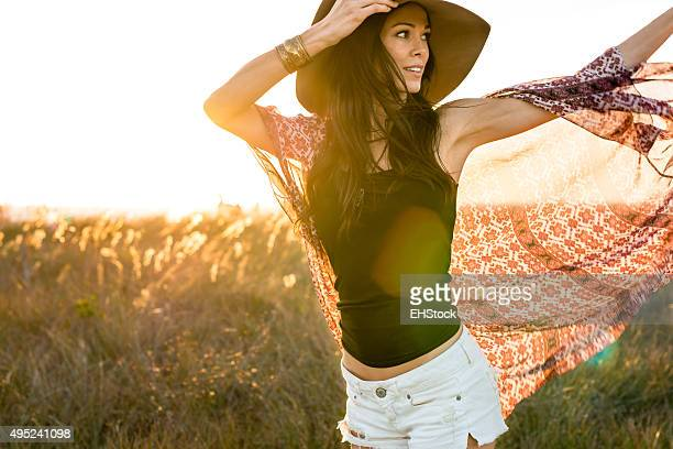 Woman in hat running through field