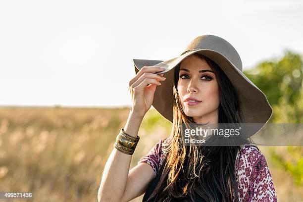 Woman in hat standing in field