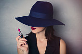 Portrait of a style brunette woman in hat with lipstick on grey background