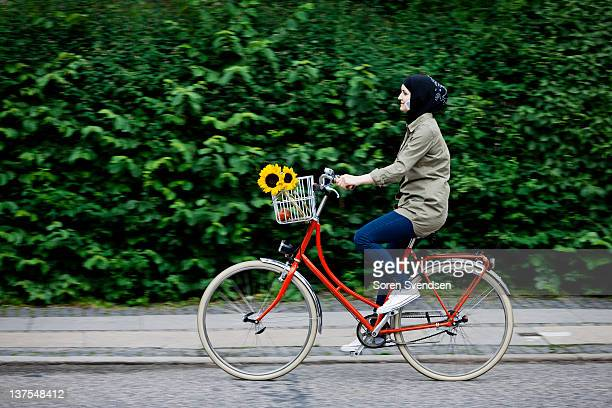 Woman in headscarf biking on cell phone