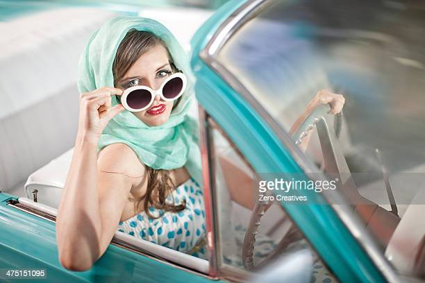 Woman in headscarf lowering sunglasses in vintage convertible