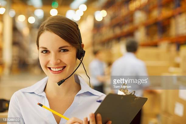 Femme dans les écouteurs tenant le presse-papier en entrepôt