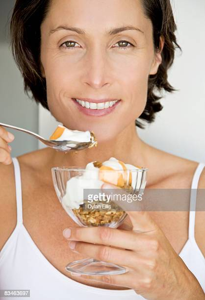 A woman in her 40s eating breakfast in her bedroom
