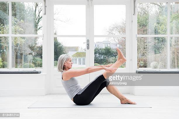Woman in her 60s stretching leg at home