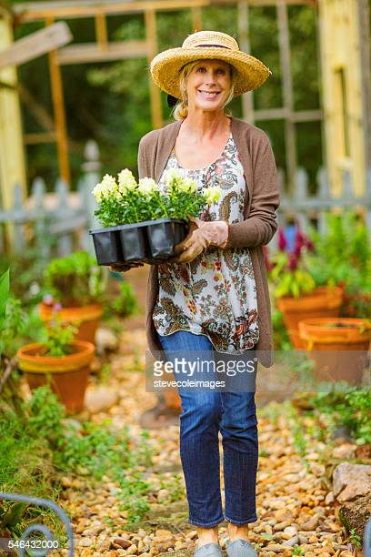 Woman in her flower garden carrying a tray full of