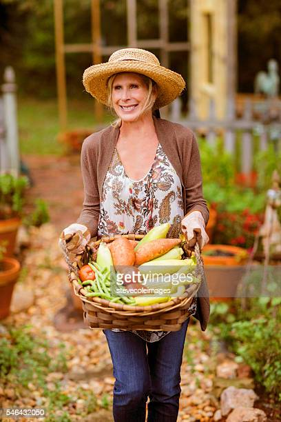 Woman in her garden carrying a basket  full of garden vegetables.