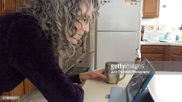 Woman in Her Kitchen Using Her Tablet