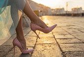 Beautiful woman legs in high heel shoes in city by sunrise