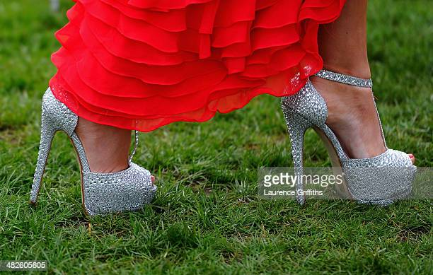 A woman in high heelswalks across the grass during Ladies day at Aintree Racecourse on April 4 2014 in Liverpool England