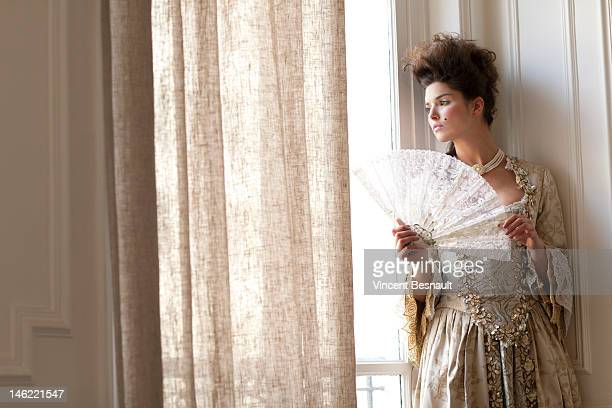 A woman in historical dress looks out of a window