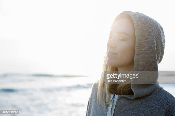 Woman in hoodie at beach