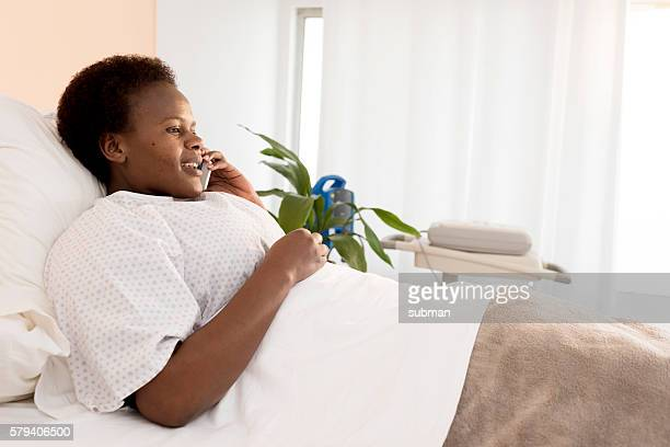 Woman In Hospital Bed Using Mobile Phone