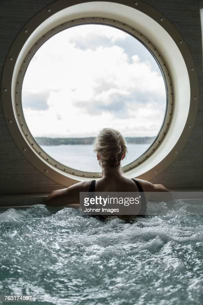 Woman in hot tub looking through window
