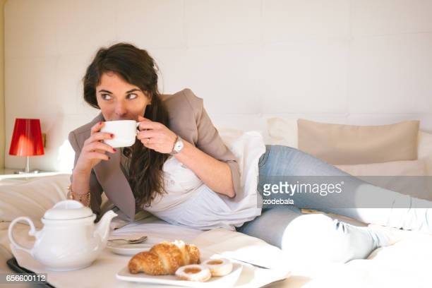 Woman in Hotel Bedroom having breakfast