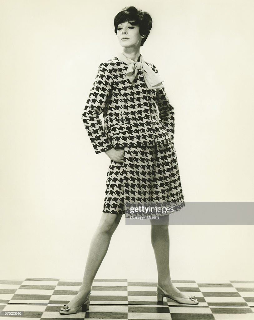 Woman in hounds tooth check suit posing in studio, portrait
