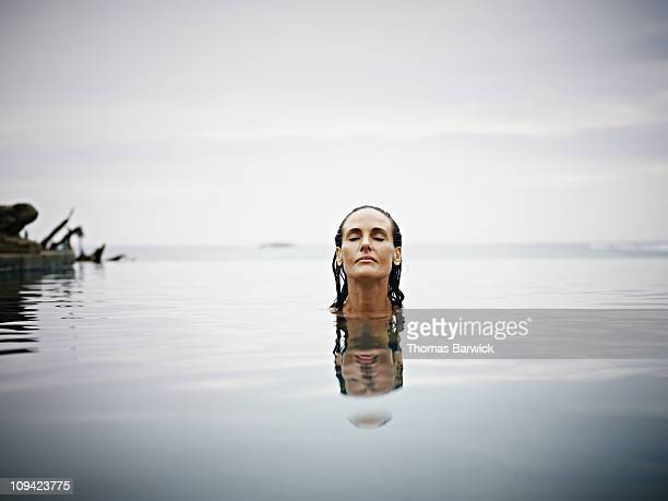 Woman in infinity pool at tropical resort