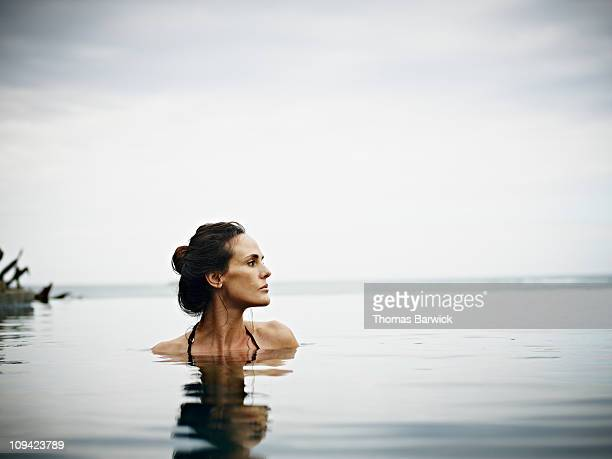 Woman in infinity pool overlooking ocean