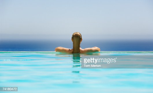 Woman in infinity pool : Stock Photo