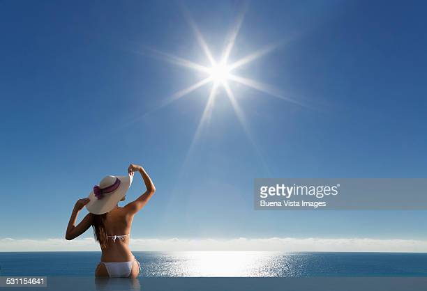 woman in infinity pool under sunshine