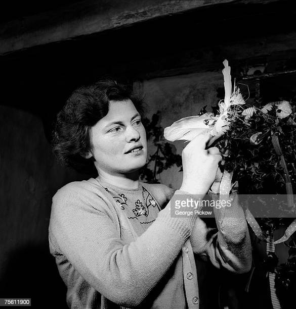 A woman in Ireland makes a 'wren' from ribbons holly and feathers ready for St Stephen's Day or 'Wren's Day' on 26th December circa 1955 The children...